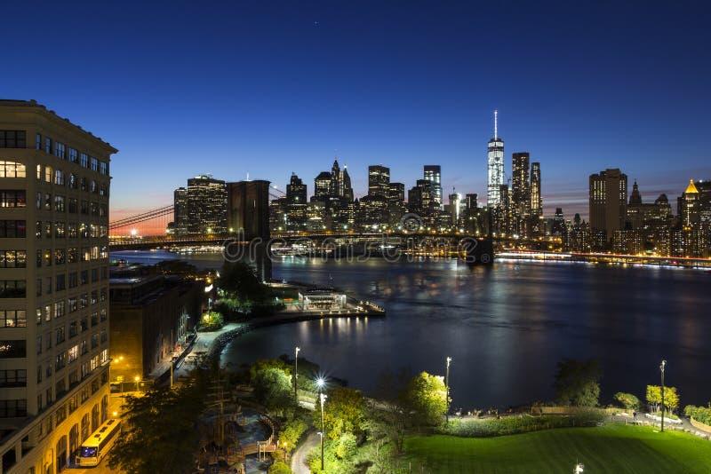 Lower Manhattan och skott för natt för Brooklyn bro fotografering för bildbyråer