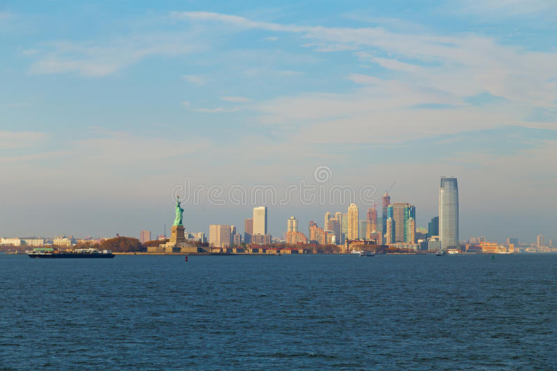 Lower Manhattan panorama and statue of Liberty in New York at dusk. stock photography