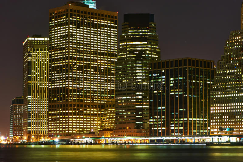 Lower Manhattanhorisontsikt på natten från Brooklyn fotografering för bildbyråer