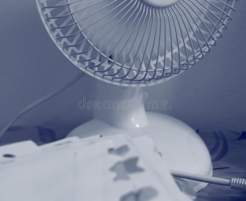 A portable table fan in working mode. The lower part/half of a table fan stands spinning in the background of slightly blurred stacked opened envelopes stock images