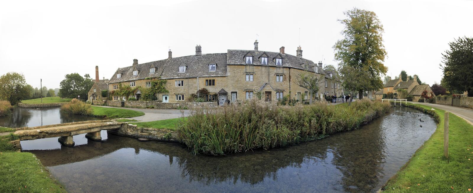 Lower slaughter cotswalds village oxfordshire uk. Panorama of the river eye winding through the quaint village of lower slaughter in oxfordshire england past royalty free stock images