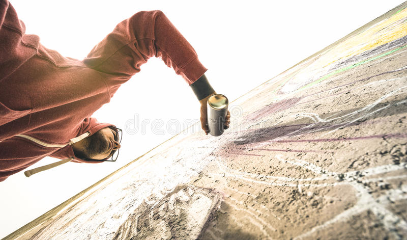 Lower view of street artist painting graffiti on generic wall stock photo