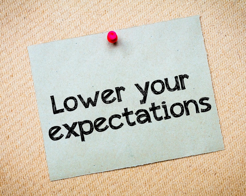 Lower your expectations. Message. Recycled paper note pinned on cork board. Concept Image royalty free stock images