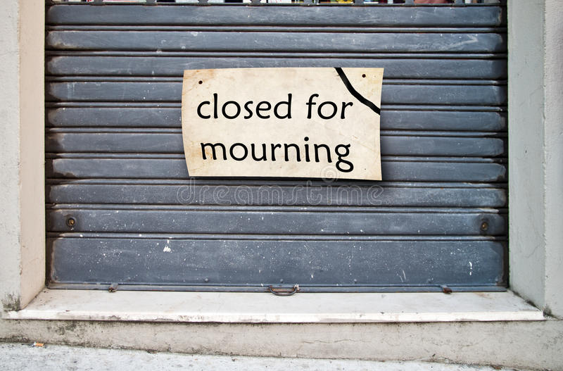 Shop closed for mourning. Lowered shutter of a shop closed due to a bereavement that hit the family royalty free stock photo