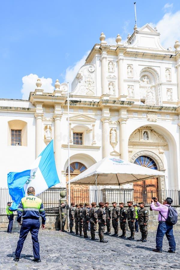 Lowering of Guatemalan flag on Independence Day, Antigua, Guatemala. Antigua, Guatemala - September 15, 2017: Soldiers lower Guatemalan flag alongside Mayor of stock images
