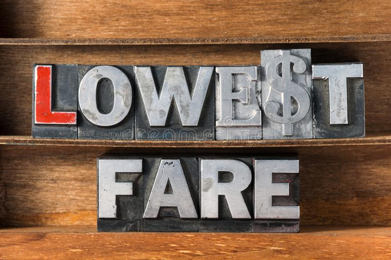 Lowest fare tray. Lowest fare phrase made from metallic letterpress type on wooden tray stock photography