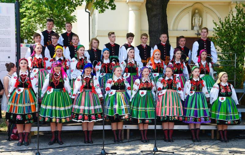 Lowicz/Polen - Maj 31 2018: Lokal, regional kör av unga kvinnor och iklädda folkloredräkter för män arkivfoto