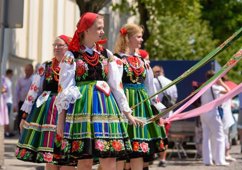 Lowicz/Polonia - 31 de mayo 2018: Procesión del día de fiesta de la iglesia del Corpus Christi Las mujeres locales se vistieron e fotografía de archivo libre de regalías