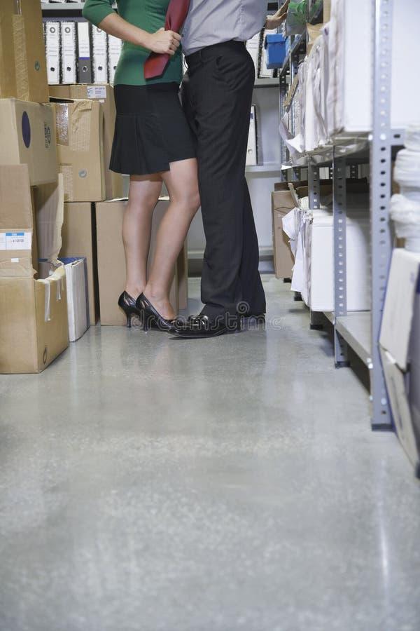 Lowsection пар обнимая в кладовой офиса стоковая фотография rf