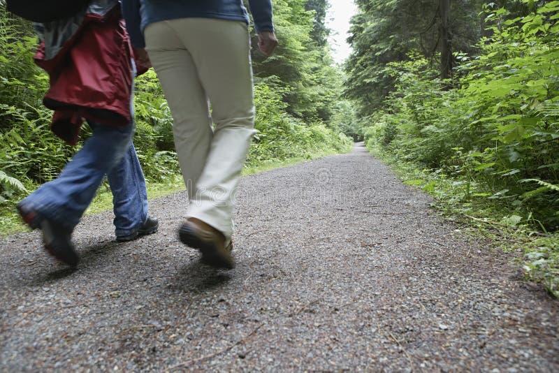 Lowsection av par som går på Forest Road arkivfoton