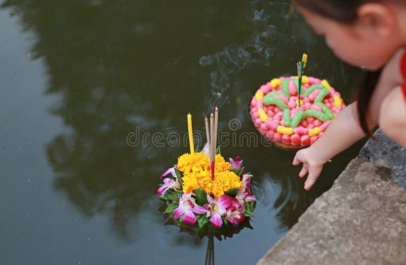 Loy Krathong节日,亚裔儿童女孩浮动krathong在饶恕女神的庆祝节日的恒河池塘在泰国 免版税库存照片