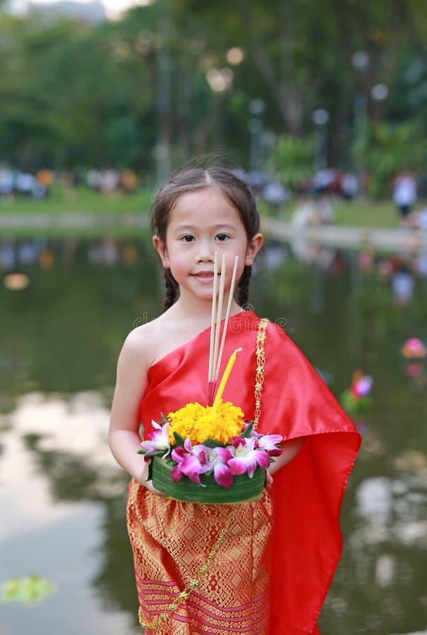 Loy Krathong-festival, Aziatisch Kindmeisje in Thaise traditionele kleding met holding krathong voor vergiffenisgodin Ganges aan royalty-vrije stock afbeeldingen