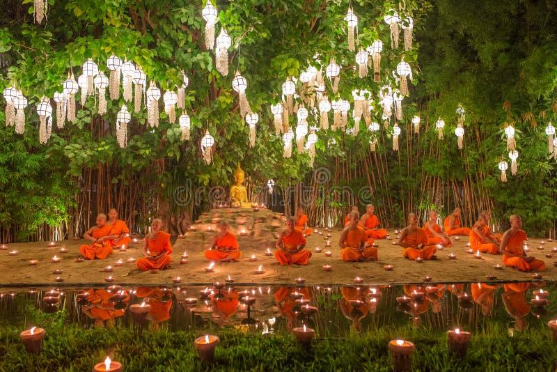 Loy Kratong节日、和尚火蜡烛对菩萨和浮动灯在帕纳陶寺, Chiangmai,泰国 免版税库存图片