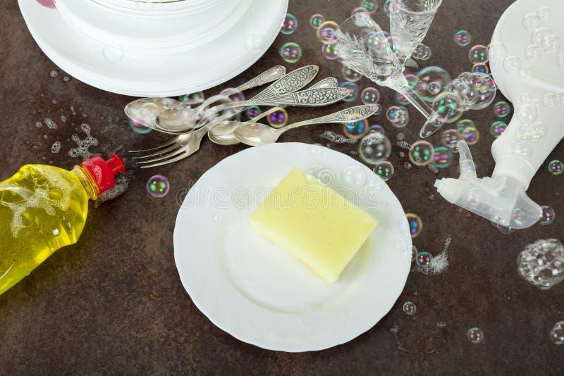 Loza lavada, botella con el detergente, burbujas de jabón en superficie oscura imágenes de archivo libres de regalías