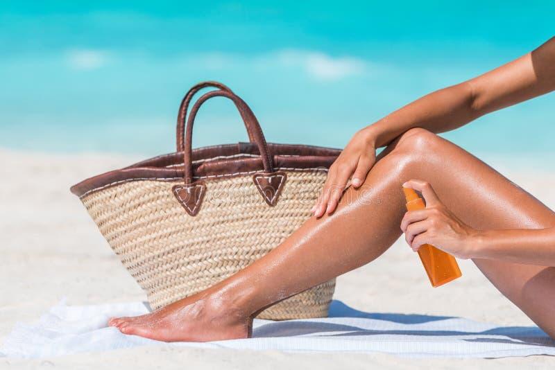Lozione solare di spruzzatura della protezione solare della donna alla spiaggia fotografia stock libera da diritti