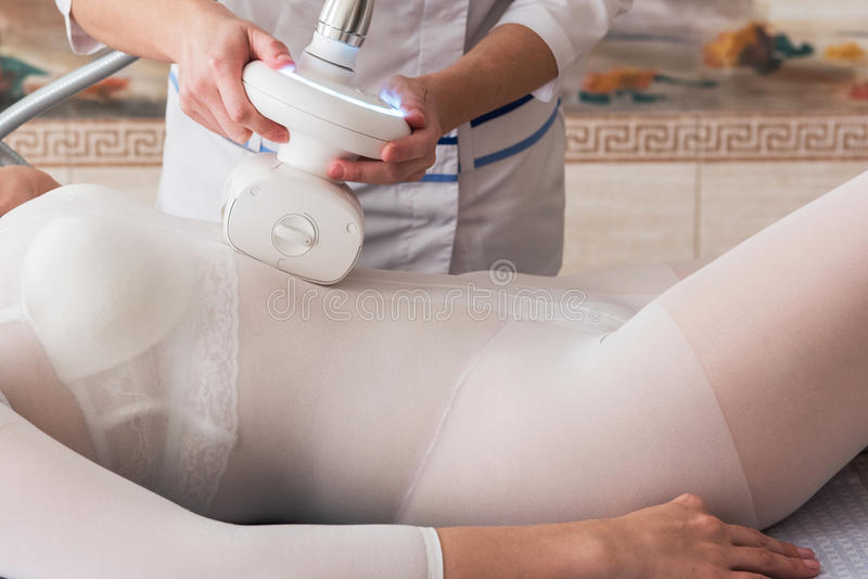 LPG, and body contouring treatment in clinic. Woman in special white suit getting anti cellulite massage in a spa salon. LPG, and body contouring treatment in stock image