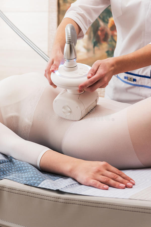 LPG, and body contouring treatment in clinic. Woman in special white suit getting anti cellulite massage in a spa salon. LPG, and body contouring treatment in royalty free stock photo