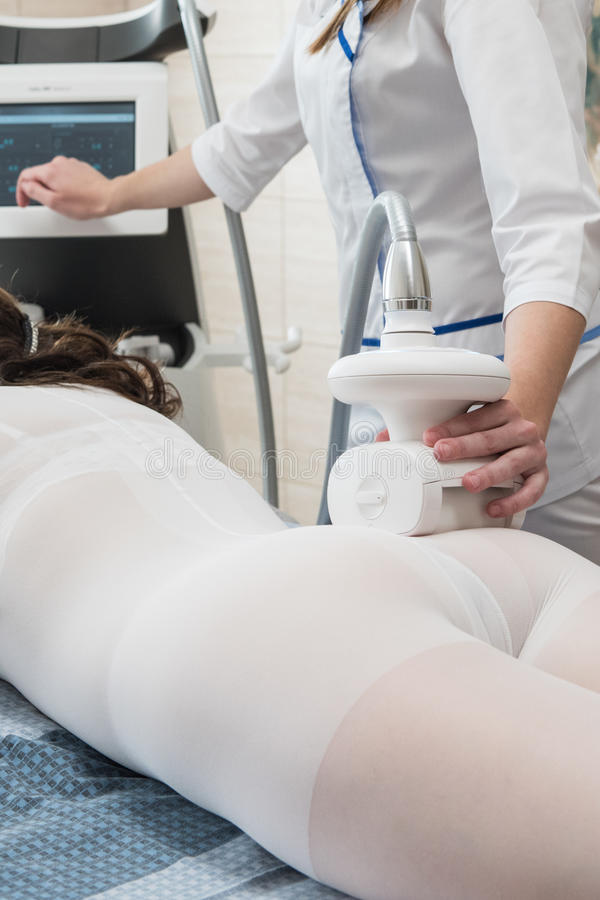LPG, and body contouring treatment in clinic. Woman in special white suit getting anti cellulite massage in a spa salon. LPG, and body contouring treatment in stock photo