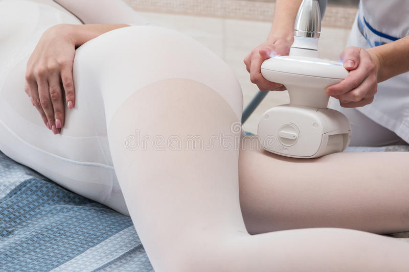 LPG, and body contouring treatment in clinic. Woman in special white suit getting anti cellulite massage in a spa salon. LPG, and body contouring treatment in royalty free stock photos