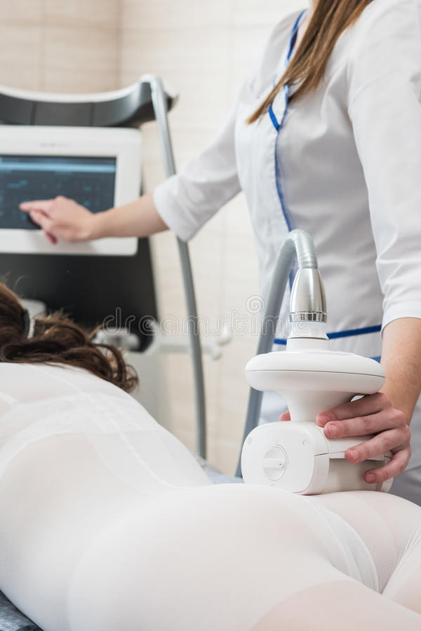 LPG, and body contouring treatment in clinic. Woman in special white suit getting anti cellulite massage in a spa salon. LPG, and body contouring treatment in stock photography
