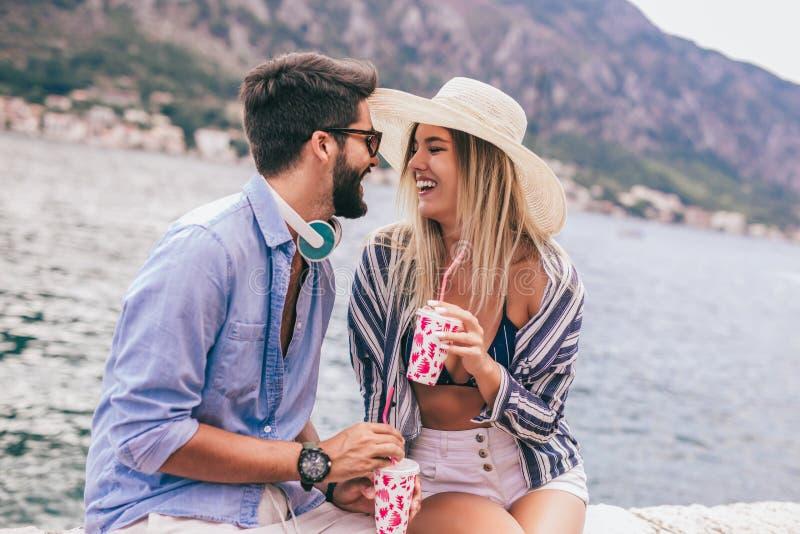 ?lska lyckliga par ha gyckel p? stranden royaltyfri bild