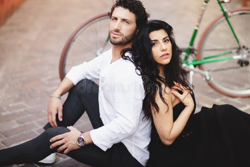 ?lska st?ende f?r par En man och en kvinna sitter på gatan av den gamla staden Bak dem är en cykel royaltyfri bild