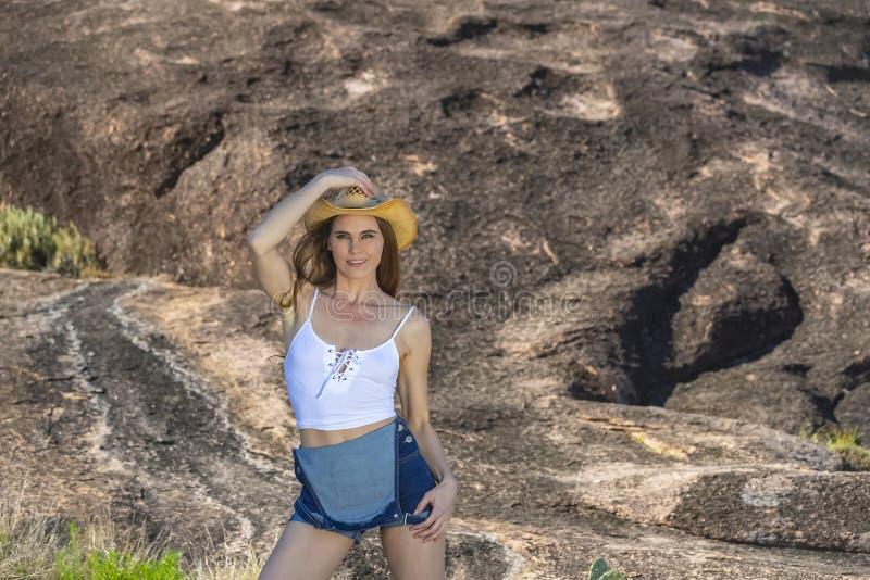 ?lskv?rd brunettcowgirlmodell Posing Outdoors royaltyfri fotografi