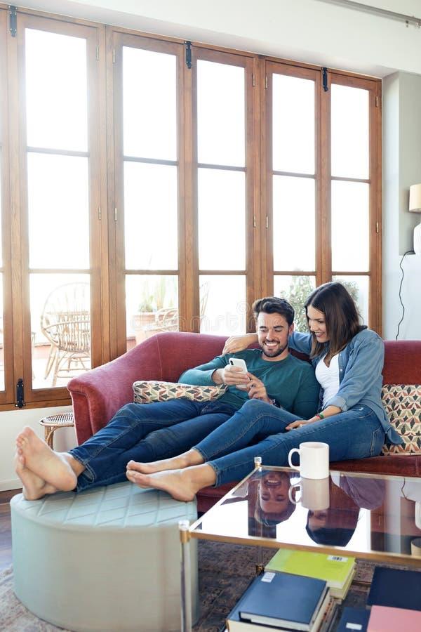 ?lskv?rda unga par genom att anv?nda dem mobiltelefon, medan sitta p? soffan hemma royaltyfri bild