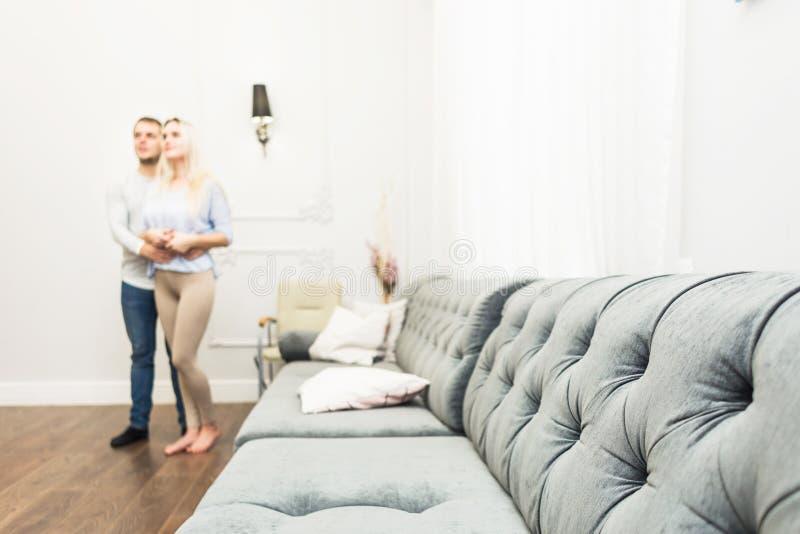 ?lskv?rda unga par i en vardagsrum med en modern inre royaltyfri bild