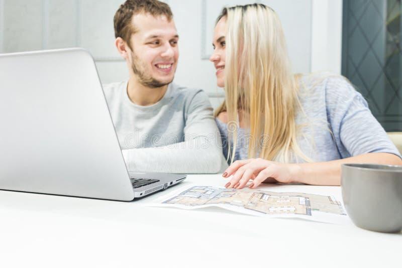 ?lskv?rda unga par och genom att anv?nda en b?rbar dator och v?lja en ny l?genhet royaltyfri bild