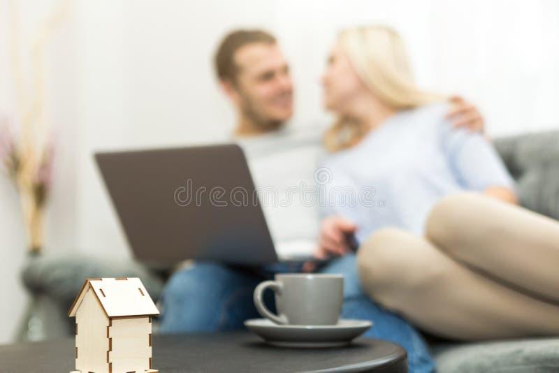 ?lskv?rda unga par och genom att anv?nda en b?rbar dator och v?lja en ny l?genhet Orientering av huset i f?rgrunden arkivfoton