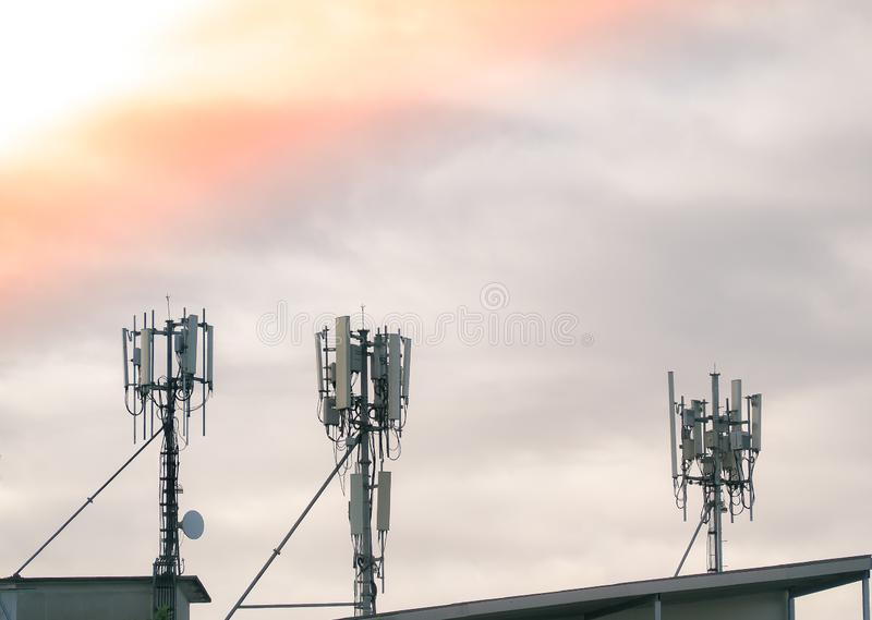 LTE, GSM, 2G, 3G, 4G, 5G tower of cellular communication on the roof. Telecommunication tower against the morning sky with clouds stock photography