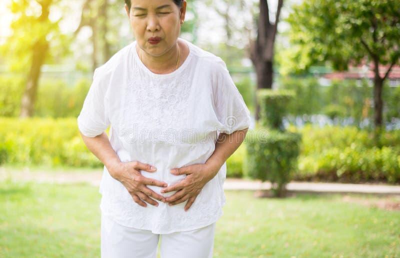 ?ltere asiatische Frau, die schmerzliche Magenschmerzen am allgemeinen Park, ?lteres weibliches Leiden von den Bauchschmerzen, Ab stockfotos