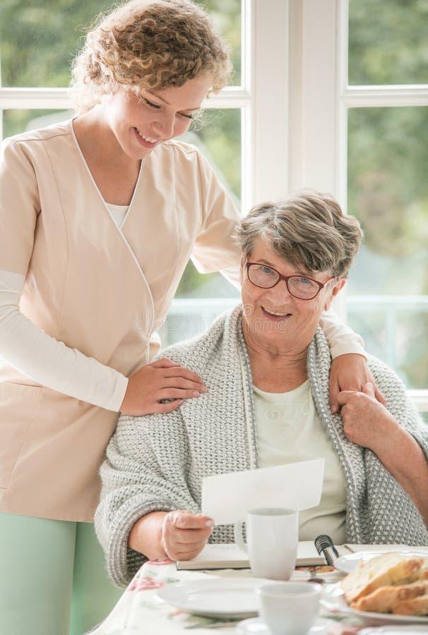 ?ltere Dame auf Rollstuhl mit jungem Freiwilligem in der beige Uniform, die sie st?tzt stockfotografie