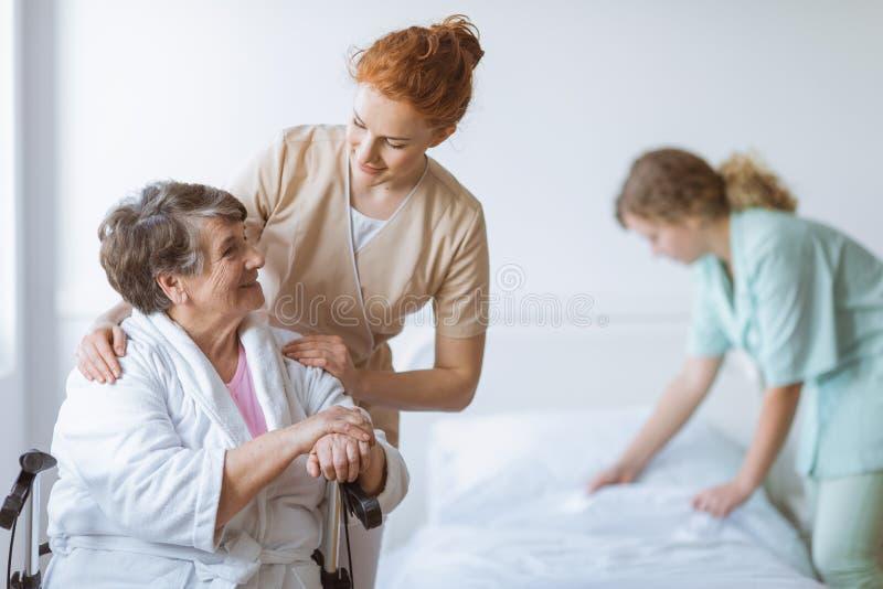 ?ltere Frau auf Rollstuhl im Pflegeheim lizenzfreies stockfoto