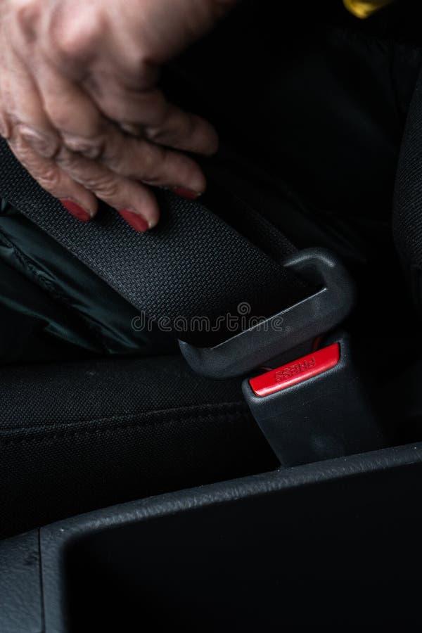 ?ltere ?ltere Frau befestigt einen Sicherheitsgurt in einem Auto, das gr?ne und gelbe Jacke tr?gt stockfotografie