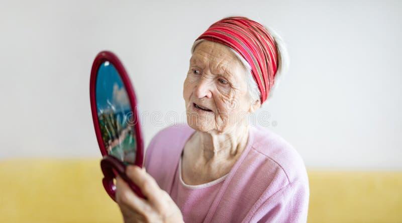 ?ltere Frau, die im Spiegel betrachtet stockfotografie