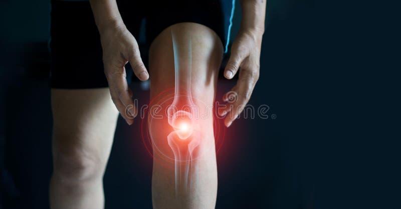 ?ltere Frau, die unter den Schmerz im Knie leidet Sehnenprobleme und gemeinsame Entzündung auf dunklem Hintergrund stockbild
