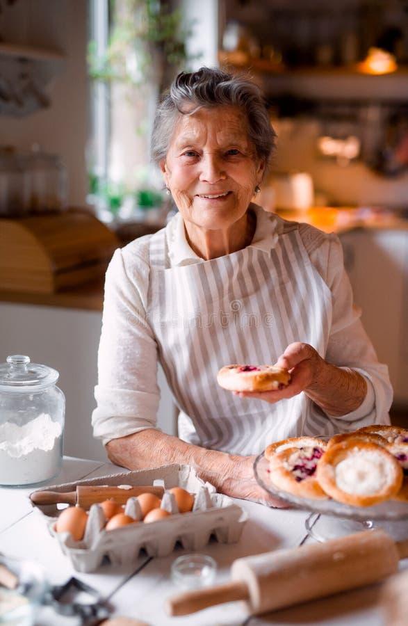 ?ltere Frau, die zu Hause Kuchen in einer K?che macht stockbild