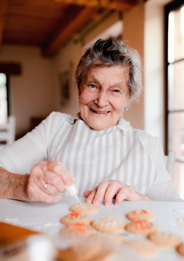 ?ltere Frau, die zu Hause Kuchen in einer K?che macht und verziert stockfotografie