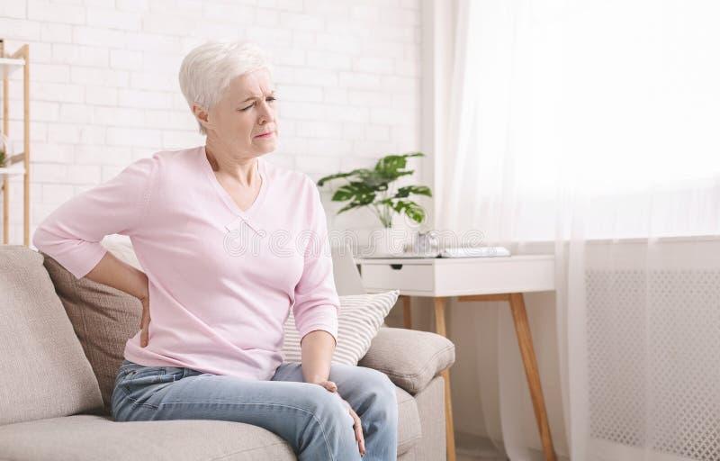 ?ltere Frau, die zu Hause unter R?ckenschmerzen leidet stockbild