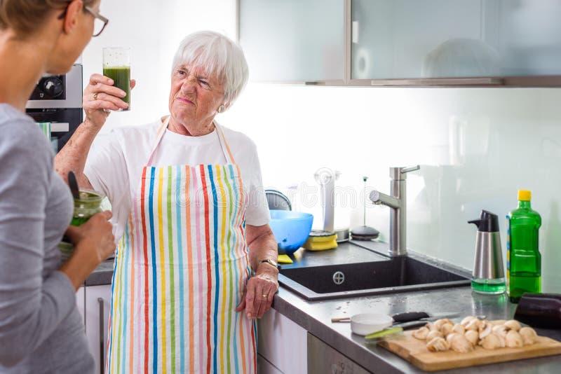 ?ltere Frau/Gro?mutter, die in einer modernen K?che mit ihrer Enkelin kocht lizenzfreie stockfotos