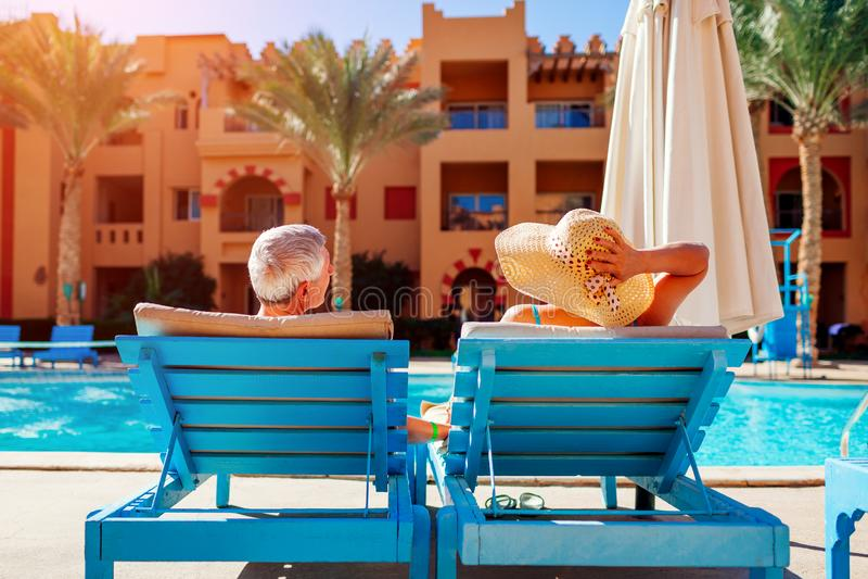 ?ltere Paare, die durch den Swimmingpool liegt auf Liegen sich entspannen Leute, die Sommerferien genie?en lizenzfreie stockfotografie
