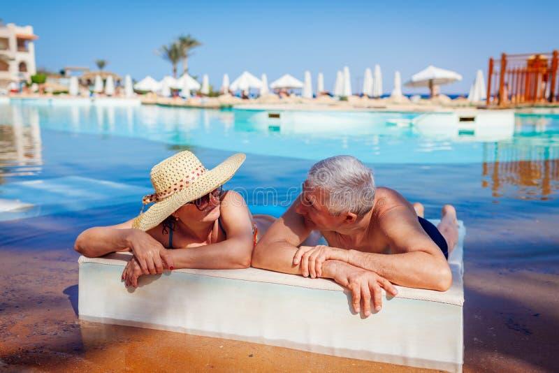 ?ltere Paare, die im Swimmingpool sich entspannen Leute, die Sommerferien genie?en lizenzfreie stockfotos