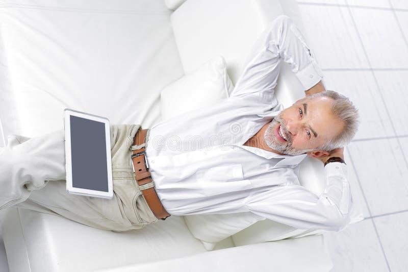 ?lterer Gesch?ftsmann, der den digitalen Tablettenschirm sitzt auf Sofa betrachtet lizenzfreie stockfotos