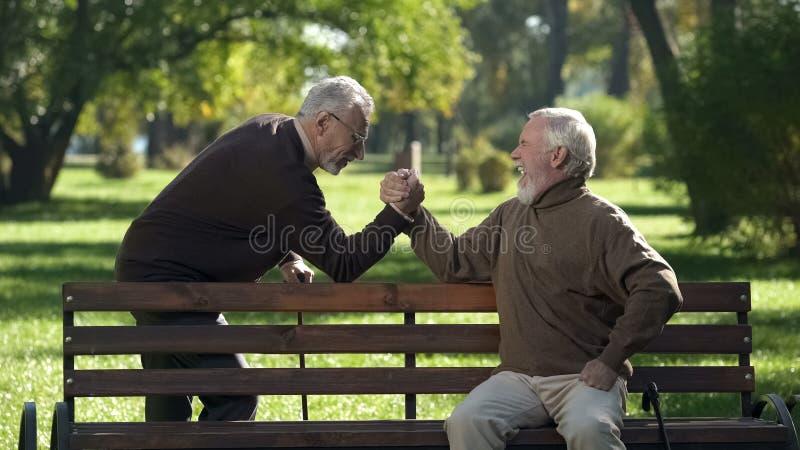 ?lterer grau-haariger m?nnlicher beginnender Armdr?ckenwettbewerb im Park, Freundschaft lizenzfreie stockfotografie