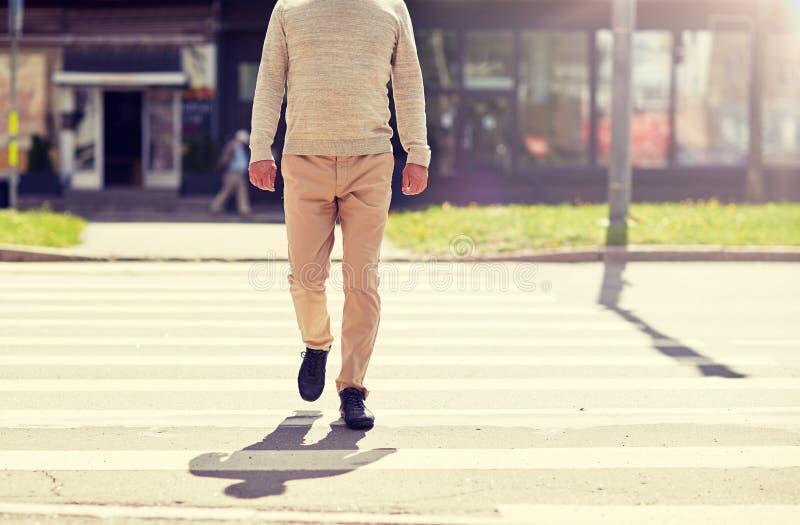 ?lterer Mann, der entlang Stadtzebrastreifen geht stockfotos
