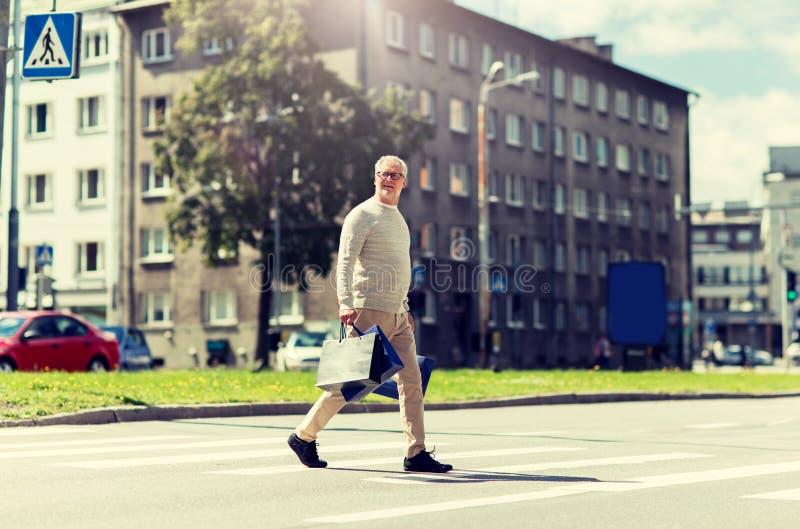 ?lterer Mann mit Einkaufstaschen gehend auf Zebrastreifen stockfotografie