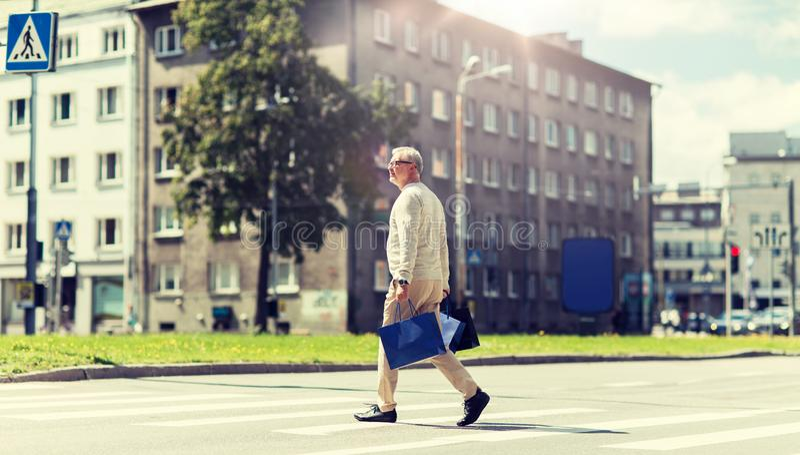 ?lterer Mann mit Einkaufstaschen gehend auf Zebrastreifen stockbild