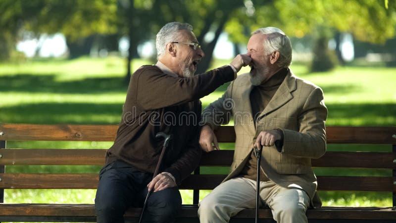 Älteres männliches Scherzen mit Freund, alte Männer, die Spaß im Sommerpark, Ruhestand haben lizenzfreies stockfoto